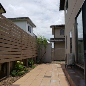 落ち着きある色合いの板塀とタイルテラス